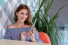 Mujer feliz joven que habla en el teléfono móvil con el amigo mientras que se sienta solamente en el interior moderno de la cafet Imagenes de archivo