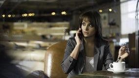 Mujer feliz joven que habla en el teléfono móvil con el amigo mientras que se sienta solamente en la cafetería moderna interior,  Fotos de archivo libres de regalías