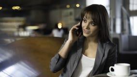 Mujer feliz joven que habla en el teléfono móvil con el amigo mientras que se sienta solamente en la cafetería moderna interior,  Imagen de archivo libre de regalías