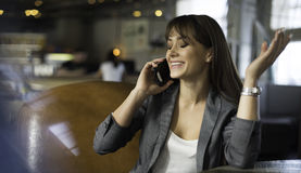 Mujer feliz joven que habla en el teléfono móvil con el amigo mientras que se sienta solamente en la cafetería moderna interior,  Foto de archivo libre de regalías