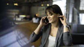 Mujer feliz joven que habla en el teléfono móvil con el amigo mientras que se sienta solamente en la cafetería moderna interior,  Imagen de archivo