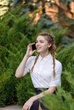 Mujer feliz joven que habla en el teléfono móvil, sentándose en parque de la ciudad Foto de archivo