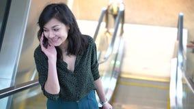 Mujer feliz joven que habla en el teléfono mientras que se coloca en la escalera móvil en la alameda