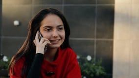 Mujer feliz joven que habla en un teléfono móvil que se sienta en una tabla en un café metrajes