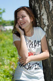 Mujer feliz joven que invita al móvil al aire libre por el árbol en el parque el día de verano Imagenes de archivo