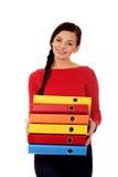 Mujer feliz joven que lleva a cabo carpetas Fotografía de archivo