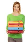 Mujer feliz joven que lleva a cabo carpetas Fotos de archivo libres de regalías