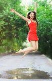 Mujer feliz joven que lleva el vestido rojo que salta en un charco Foto de archivo