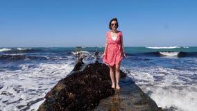 Mujer feliz joven que lleva el vestido rojo y las gafas de sol que se colocan en el embarcadero con las ondas del mar que golpean almacen de metraje de vídeo