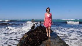Mujer feliz joven que lleva el vestido rojo y las gafas de sol que se colocan en el embarcadero con las ondas del mar que golpean metrajes