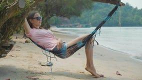 Mujer feliz joven que miente en la hamaca en la playa arenosa en la cámara lenta almacen de video