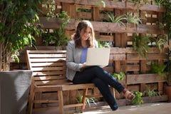 Mujer feliz joven que mira el ordenador portátil en el banco en la calle w imagen de archivo