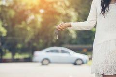 Mujer feliz joven que muestra la llave del nuevo coche Foto de archivo libre de regalías