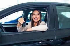 Mujer feliz joven que muestra la llave del nuevo coche imagen de archivo