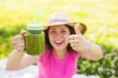 Mujer feliz joven que muestra los pulgares para arriba con los smoothies verdes en una comida campestre Comida, detox y concepto  foto de archivo libre de regalías