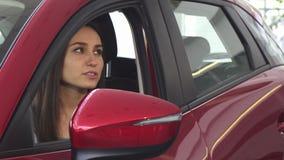 Mujer feliz joven que recibe llaves del coche a su nuevo automóvil metrajes