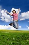 Mujer feliz joven que salta arriba contra el cielo azul Fotografía de archivo libre de regalías