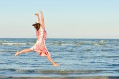 Mujer feliz joven que salta arriba en la playa Fotografía de archivo