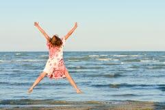 Mujer feliz joven que salta arriba en la playa Fotos de archivo libres de regalías