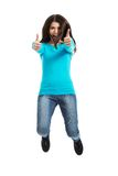 Mujer feliz joven que salta con los pulgares para arriba Imágenes de archivo libres de regalías