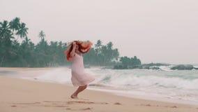 Mujer feliz joven que salta en la playa del océano almacen de metraje de vídeo