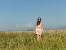 Mujer feliz, joven que se coloca en campo verde Foto de archivo libre de regalías