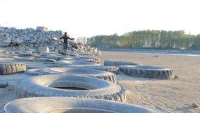 Mujer feliz joven que se divierte, corriendo en los neumáticos en el tiempo de la puesta del sol almacen de metraje de vídeo