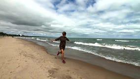Mujer feliz joven que se ejecuta en una playa almacen de video