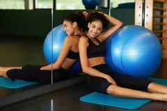 Mujer feliz joven que se relaja después de la clase de Pilates que se sienta con la bola del ajuste en la estera Fotografía de archivo libre de regalías