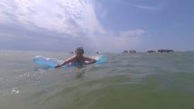 Mujer feliz joven que se relaja en el colchón inflable en el mar metrajes
