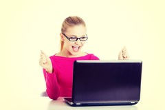 Mujer feliz joven que se sienta delante del ordenador portátil Fotos de archivo libres de regalías