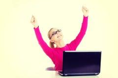 Mujer feliz joven que se sienta delante del ordenador portátil Imagen de archivo