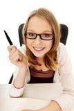 Mujer feliz joven que se sienta en el escritorio Imagen de archivo libre de regalías