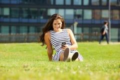 Mujer feliz joven que se sienta en hierba usando móvil Fotografía de archivo