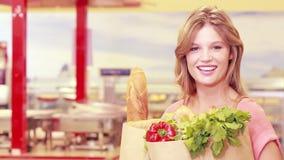 Mujer feliz joven que sonríe en la cámara con las mercancías compradas almacen de video