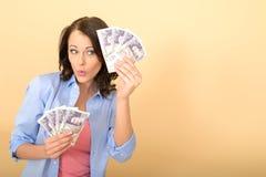 Mujer feliz joven que sostiene el dinero que parece satisfecho y encantado Foto de archivo