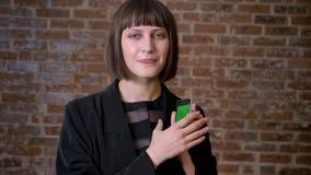Mujer feliz joven que sostiene el teléfono con chromakey y que muestra los pulgares para arriba, fondo de la pared de ladrillo almacen de metraje de vídeo