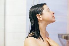 Mujer feliz joven que toma la ducha en casa o el cuarto de ba?o del hotel La muchacha morena hermosa que se lava el pelo y que go imagen de archivo libre de regalías