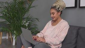 Mujer feliz joven que usa el ordenador portátil y sonriendo en el sofá en casa almacen de metraje de vídeo