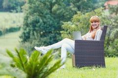 Mujer feliz joven que usa el ordenador portátil Imagenes de archivo