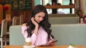 Mujer feliz joven que usa la tableta en un café almacen de metraje de vídeo