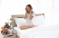 Mujer feliz joven y hermosa caucásica que se sienta en la cama matrimonial cómoda en el dormitorio interior moderno o mínimo d imágenes de archivo libres de regalías