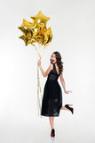 Mujer feliz juguetona atractiva que mira detrás y que sostiene los globos de oro Fotografía de archivo