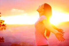 Mujer feliz libre que disfruta de puesta del sol de la naturaleza Imagen de archivo libre de regalías