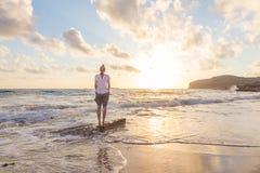 Mujer feliz libre que disfruta de puesta del sol en Sandy Beach Fotografía de archivo libre de regalías