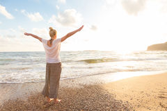 Mujer feliz libre que disfruta de puesta del sol en Sandy Beach Imágenes de archivo libres de regalías
