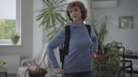 Mujer feliz madura en la sudadera con capucha azul que fija la mochila cómoda negra en su parte posterior metrajes