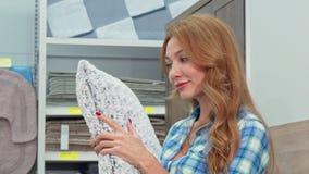 Mujer feliz magnífica que elige las almohadas en la tienda del mobiliario metrajes