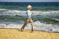 Mujer feliz mayor que corre en la playa a lo largo de la costa cerca del mar Fotografía de archivo libre de regalías