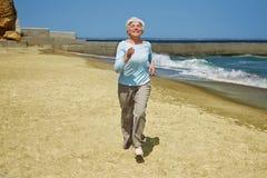 Mujer feliz mayor que corre en la playa a lo largo de la costa cerca del mar Fotos de archivo libres de regalías